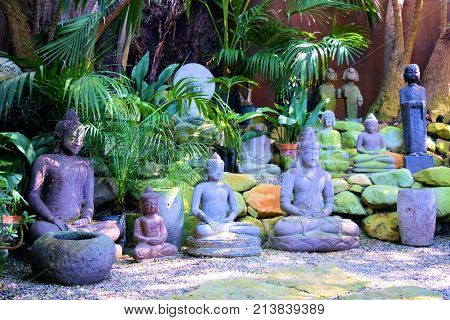 Buddha sculptures surrounded by lush green tropical plants taken on a patio in a Zen Meditation Garden