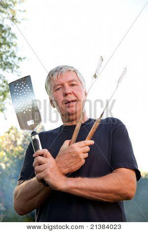 Mature man wields cooking utensils for a BBQ.