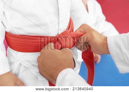 Karate instructor tying belt on child's waist, closeup