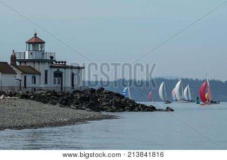 View of Seattle sailboat race with West Point Lighthouse in the foreground.