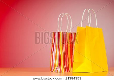 Colourful paper shopping bags against gradient background poster