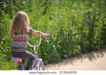 Girl rides velocipede on a country road.