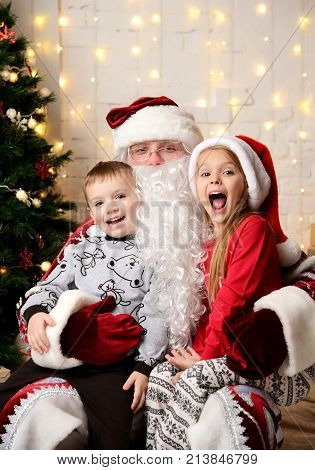 Santa Claus sitting with happy little kids cute children boy and girl near Christmas tree at home
