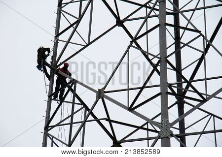 workers on the energy pole. A grid of newly installed energy pole with employees. autumn season