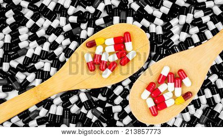 Colorful of antibiotics capsule pills in wooden spoon on black and white background of capsules. Drug resistance concept. Antibiotics drug use with reasonable and global healthcare concept.