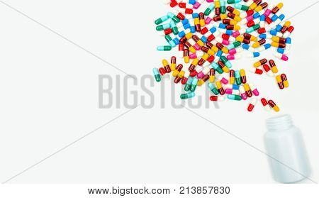 Pouring antibiotics capsule pills into plastic bottle isolated on white background with copy space. Drug resistance concept. Antibiotics drug use with reasonable and global healthcare concept.