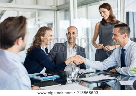 Handshake to seal a deal after a meeting. Two successful business people shaking hands in front of their colleagues. Mature businesswoman shaking hands to seal a deal with smiling businessman.