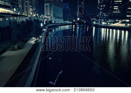 Chicago city riverwalk promenade at night with illuminated urban downtown buildings.