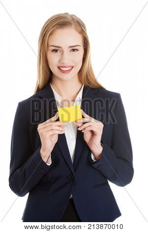 Beautiful caucasian business woman holding yellow empty personal card.