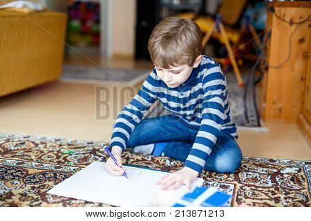 Cute little preschool kid boy at home making homework, painting a story with colorful pens. Little child writing with pencils, indoors. Elementary school and education, imagine fantasy concept.
