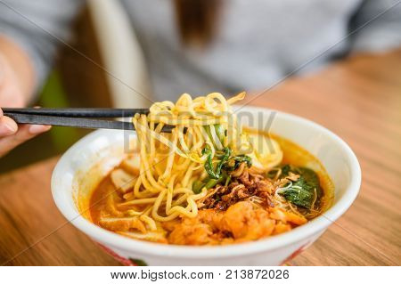 Hand with Chinese chopsticks eating noodle a famous Malaysia prawn noodle cerry soup.