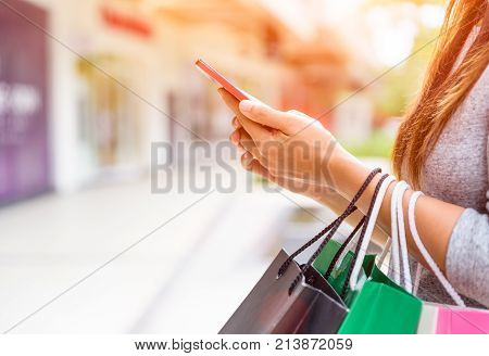 Woman holding shopping bags doing online shopping on her mobile phone in the supermarket. Black Friday sale concpt.