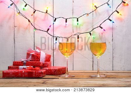 Celebration On Christmas . 2 Wine Glass And Gift Boxes On Wood Table With Electric Blinker Illuminat