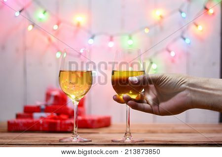 Celebration On Christmas . Adult Hand Holding A Glass Of Wine , Gift Boxes On Wood Table With Electr