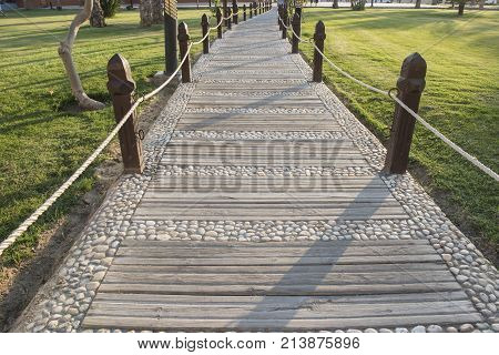 Ornate footpath through formal landscaped gardens with wooden posts in grounds of a luxury tropical hotel resort