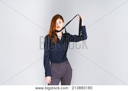 red-haired girl with red lips and in a black blouse trying to strangle herself with a tie, isolated