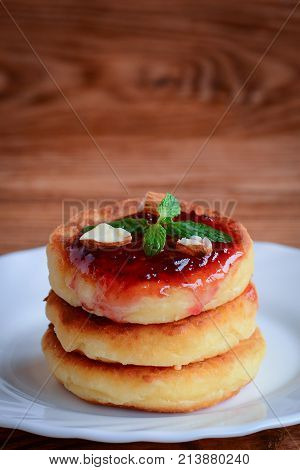 Delicious homemade cottage cheese pancakes. Simple cottage cheese pancakes with berry jam and nuts. Vertical photo. Closeup