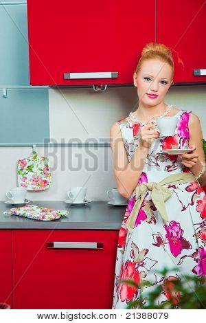 Blond woman with cup of coffee in interior of kitchen