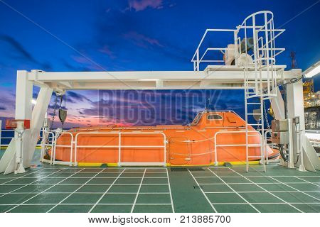 Life boat survival craft or rescue boat at oil and gas platform for emergency evacuate at muster station.