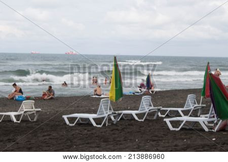 A nasty day. View of the beach. tourists sunbeds and umbrellas on summer day. Travel or sea vacations concept