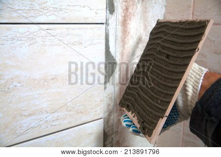 laying of tiles industrial construction worker installing small ceramic tiles on bathroom walls and applying mortar with trowel