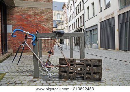 A broken bicycle is in the deserted street of Antwerp. Bicycles of Antwerp. Belgium is a country of bicycles. A bicycle on the street.