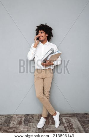 Full length portrait of a young afro american man talking on mobile phone while standing and holding binders isolated over gray background