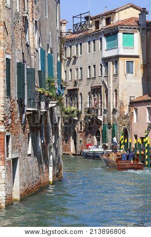 VENICE ITALY - SEPTEMBER 22 2017: City tour by tourists with motorboatside narrow channel. Communication in the city is done by water which creates a network of 150 channels interconnected.