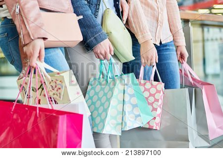 Three women with many shopping bags as a symbol of consumption and purchasing power