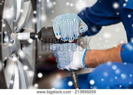 car service, repair, maintenance and people concept - auto mechanic hands with screwdriver changing tire at workshop over snow