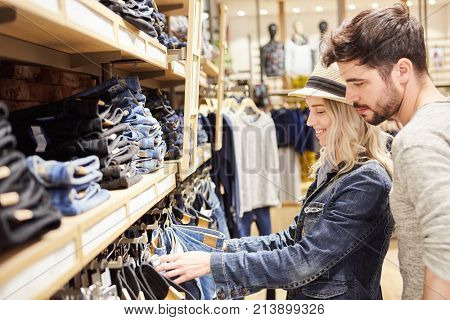 Young couple shopping at retail looking for jeans in fashion store