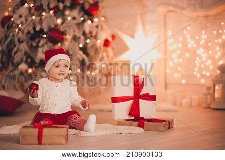 Cute baby holding Christmas ball wearing Santa Claus hat sitting with presents over Christmas tree in room. Holiday season.