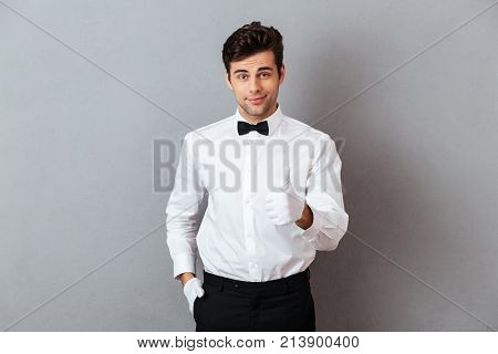 Portrait of a smiling young male waiter dressed in unifrom pointing finger at camera isolated over gray background