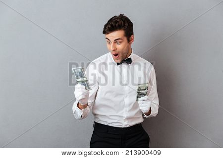 Portrait of a successful cheerful male waiter dressed in unifrom holding bunch of money banknotes isolated over gray background