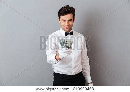 Portrait of a confident attractive male waiter dressed in unifrom giving bunch of money banknotes isolated over gray background