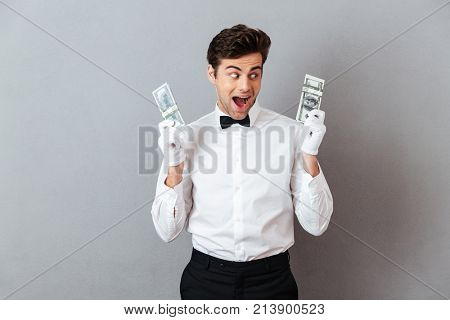 Portrait of a joyful cheery male waiter dressed in unifrom holding bunch of money banknotes isolated over gray background