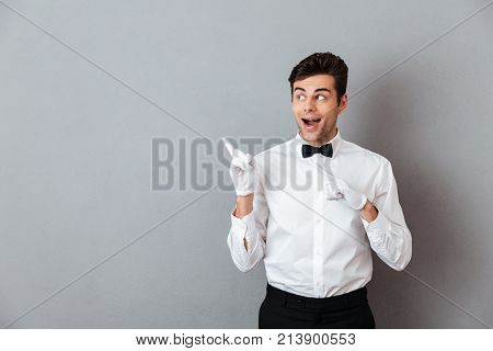 Portrait of an excited cheerful male waiter dressed in unifrom pointing finger away at copy space isolated over gray background