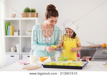 family, cooking, baking and people concept - happy mother with cupcake liner and little daughter with spoon pouring batter and making muffins at home kitchen
