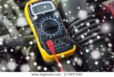 auto service, repair and maintenance concept - digital multimeter or voltmeter testing car battery over snow