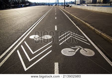 Separate bicycle lane for riding bicycles. White painted bike on asphalt. Ride ecological green urban transport