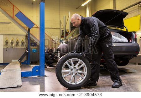 car service, repair, maintenance and people concept - auto mechanic man changing tire at workshop