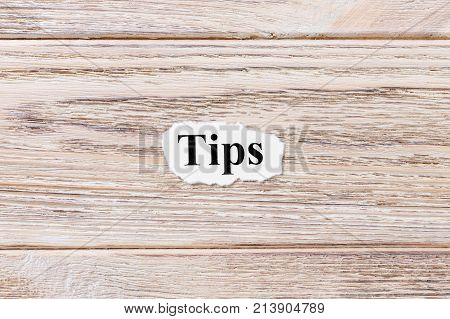 TIPS of the word on paper. concept. Words of TIPS on a wooden background.