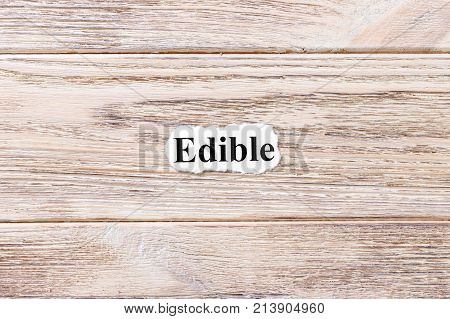 EDIBLE of the word on paper. concept. Words of EDIBLE on a wooden background.