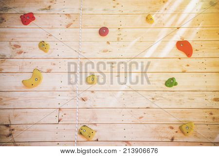 Colorful hand and footholds on a wooden climbing wall in a close up view for a recreational challenge or for practising for the extreme sport of rock climbing with the sun glow in the right corner