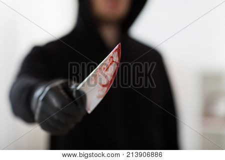 murder, kill and people concept - close up of criminal or murderer with blood on knife at crime scene