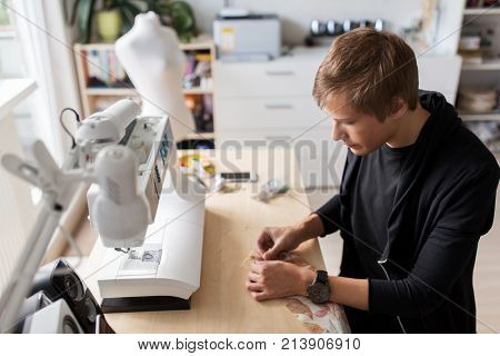 tailoring, sewing and clothing concept - fashion designer with cloth and pins making new dress at home studio or workshop