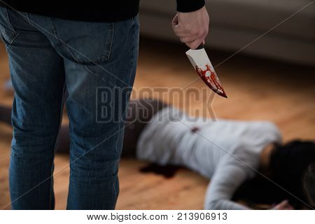 murder, kill and people concept - criminal or murderer with knife in blood and dead woman body lying on floor at crime scene