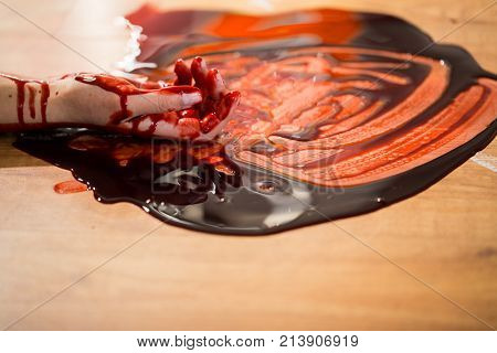 murder, kill and people concept - dead woman hand in blood on floor at crime scene