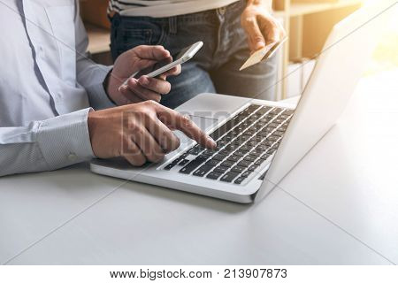 Man using smart phone and credit/debit card register payments online shopping and customer service network connection market using technology on laptop Internet Online shopping or banking concept.