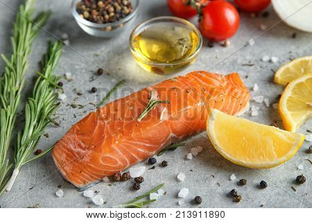 Slice of salmon fillet and ingredients for marinade on table
